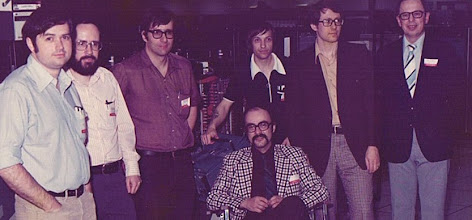 Photo: From the left, standing, John Hogg (UBC), Mike Alexander (UM), Alan Davis (UQV), John Stasiuk (UQV), Gerry Gabel (UQV), Henry Ewasechko (UQV) and seated Dr. Dale Bent (UQV) at the Amdahl Benchmarking Center, Sunnyvale, CA, USA, fall 1974