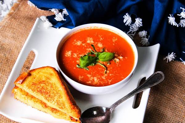 A Bowl Of Spicy Crock Pot Tomato Bisque With A Grilled Cheese Sandwich.