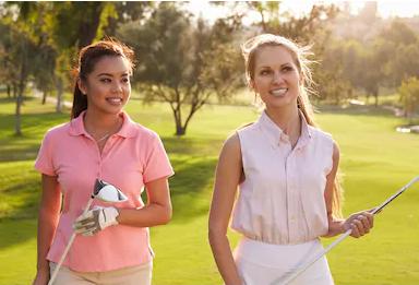 Усмихнати жени със стикове за голф на игрището