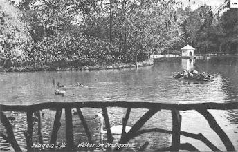 Photo: Eine im April 1912 abgestempelte Ansichtskarte zeigt den Schwanenteich mit inaktiver Fontäne von dem Oberen der beiden Pavillons aus. Der hintere Teil des Teiches bei der Brücke und dem Vogelunterstand ist noch mittels eines Zaunes abgesperrt.
