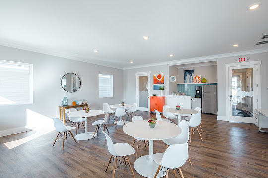 Community lounge area with modern seating tables and decorative accents with access to a kitchen area