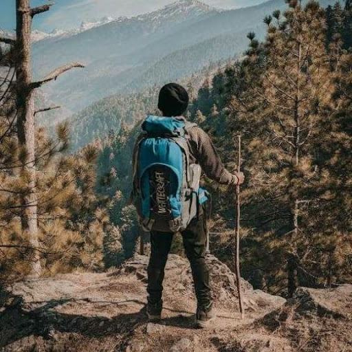 A young man wearing a turquoise backpack standing atop a vista overlooking the Himalayas.