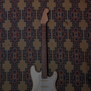 Guitar leaning against wall with patterned wallpaper
