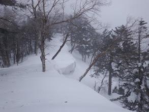 雪庇の脇を進む