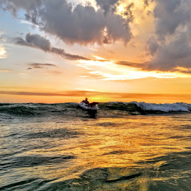 Mounting his board in the gulf of Mexico by Jeffrey Lee - Landscapes Sunsets & Sunrises