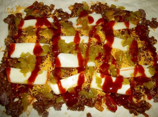 Spread 1 cup cheddar cheese evenly, 1/2 the muenster cheese slices, 1/2 the chiles....