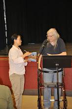 Photo: Qiaolan Wan hands Mary K. Whittington the RASP poetry anthology.