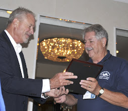 Photo: Barry Ladendorf presents convention coordinator Gary Butterfield with a plaque of appreciation
