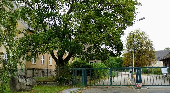 Großes Grundstück mit Bäumen und Gebäuden von Stacheldraht bewehrtem Metallgitterzaun umgeben.