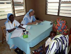 Photo: trois matinées par semaine soeur Séréna consulte en moyenne 80 malades qui se pressent dès 7 heures dans la salle d'attente qui ne désemplie pas avant midi. Une jeune infirmière lui vient en aide et s'initie à ce dur labeur