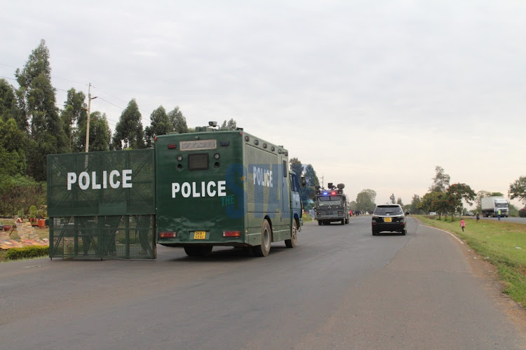 Vehicles go past a police barricade at a checkpoint meant to indicate border of Kiambu and Murang'a counties in BluePost area, Thika on March 27, 2021