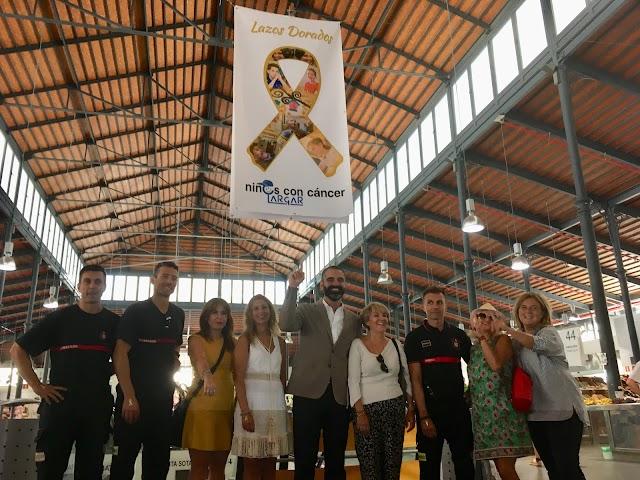 El alcalde y ARGAR presentando el lazo dorado en el Mercado Central