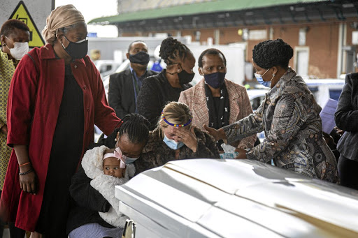 Lindsay Myeni, the wife of the late Lindani Myeni, is comforted by friends and family as his remains arrive in SA on the weekend.