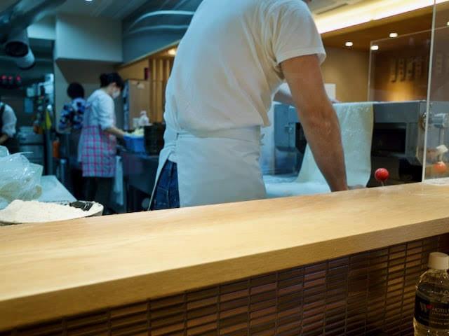 厨房内でうどんを伸ばす大将と、うどんを作る女性店員さん