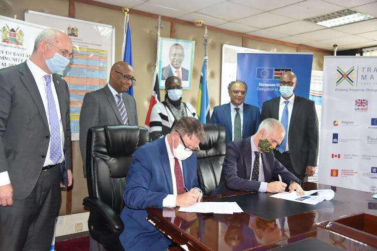 EU Ambassador Simon Mordue signs a contract withTradeMark East Africa CEO Frank Matsaert for a €5 million grant for Safetrade grant on June 16.