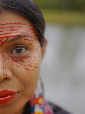 A close-up view of a woman's face with red hand painted designs on her face.