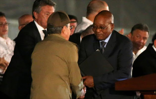 Cuban President Raul Castro (L) and South Africa's President Jacob Zuma shake hands as they attend a massive tribute to Cuba's late President Fidel Castro in Revolution Square in Havana, Cuba, November 29, 2016.