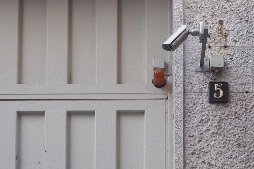 white wooden door near gray security camera