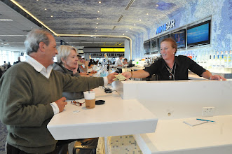 """Photo: Bernardo Rouira, left, pays bartender Dayna Delaney, right, for drinks that he and he and his wife, Alejandra Ruiz, had at a new bar, Minnibar, located on Concourse G at the Minneapolis St. Paul airport  on September 5, 2012. The couple, who are  from Buenos Aires, Argentina, were headed back home after a trip to Canada. """"We arrived at the gate and the first thing we said when we saw this place, is """"It's really nice"""","""" said Ruiz.  (Pioneer Press: Ginger Pinson)"""
