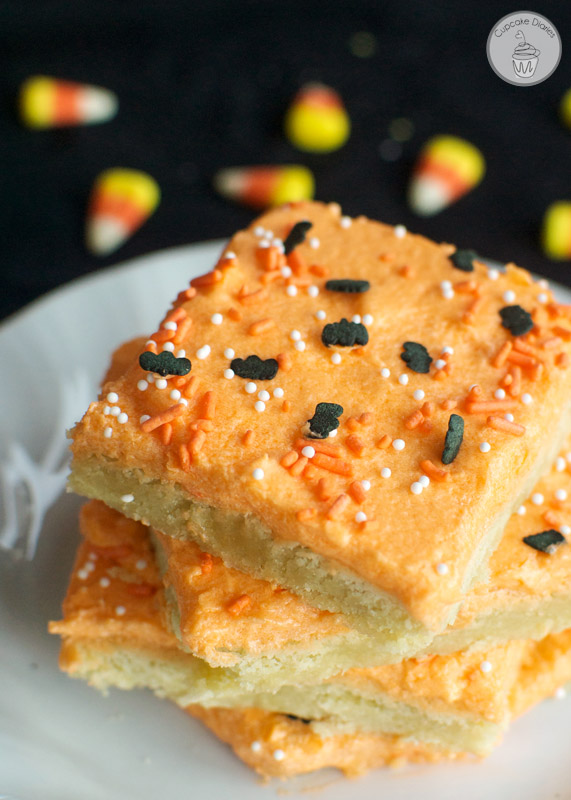 Photo of a stack of sugar cookie bars with light orange frosting and black bat sprinkles on top.