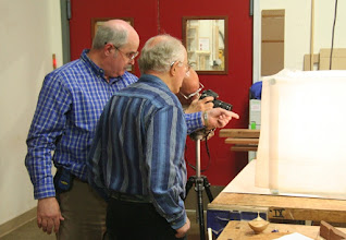 Photo: Steve Drake points out some of his very appropriately NIH-oriented turnings to Phil Brown, who is collecting pieces for our exhibit at the NIH Center.