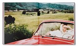 vrouw kijkt naar naast haar zittende, niet zichtbare, bestuurder van een rode auto met open kap op platte land