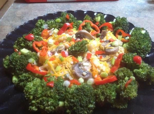 Pour rice onto a large platter, then arrange broccoli flowerets around platter of rice,...