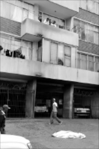 TRAGIC END: A man walks past the body of a woman on Olivia Street in Berea. She fell from the eight floor of her apartment building to escape a fire that was caused by an electrical fault. Pic. Vathiswa Ruselo. 06/10/08. © Sowetan.