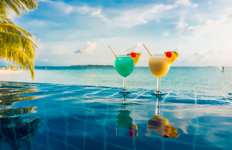 Cocktails in the swimming pool against the background of the Indian Ocean, Maldives