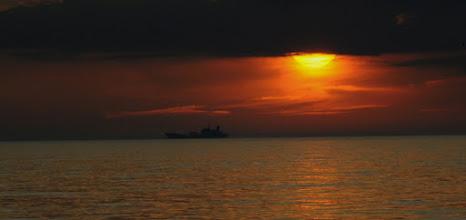 Photo: Schiff im Sonnenuntergang mit schwarzer Wetterfront