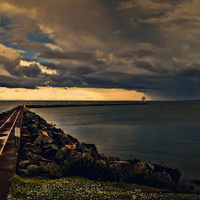 Stormn Clouds and Lighthouse by Marilyn Magnuson - Landscapes Waterscapes ( lightouse, raining, pier, lake superior, storm clouds )
