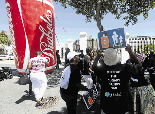 Protesters gather outside parliament in Cape Town where the first round of oral submissions was held yesterday as part of the hearings into a proposed 'sugar' tax on soft drinks, energy drinks and sweetened milk.