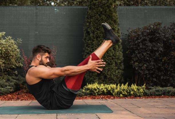 Young muscular man doing strength exercise outdoor. Shot of a shirtless muscular young man doing strength exercise on yoga mat in the backyard. abdominal workouts stock pictures, royalty-free photos & images
