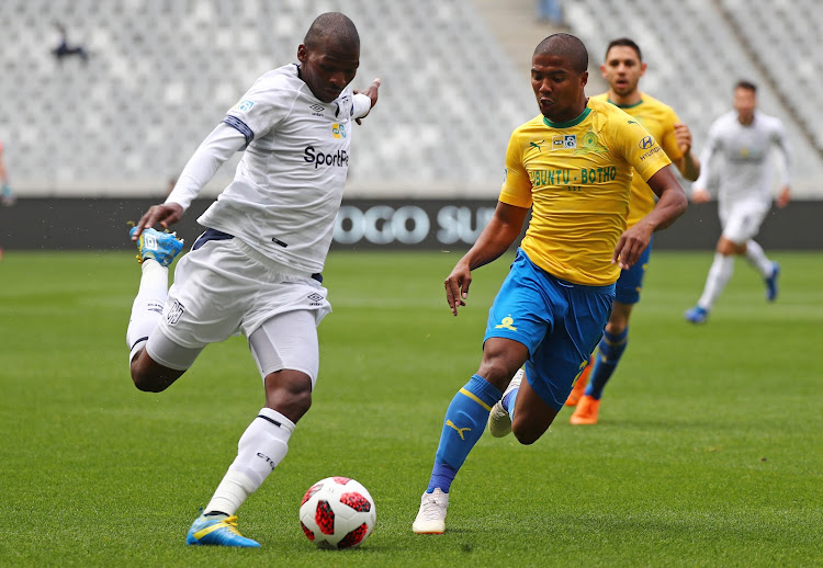 Cape Town City captain Thamsanqa Mkhize (L) releases a pass under the watchful eye of Mamelodi Sundowns defender Lyle Lakay during the MTN8 semifinal first leg match at Cape Town Stadium in Cape Town on August 25 2018.