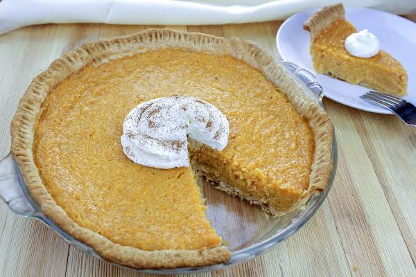 Sweet Potato Buttermilk Pie With A Piece Cut Out.