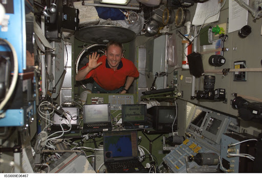 Fincke waves as he enters the Zvezda Service Module during Expedition 9