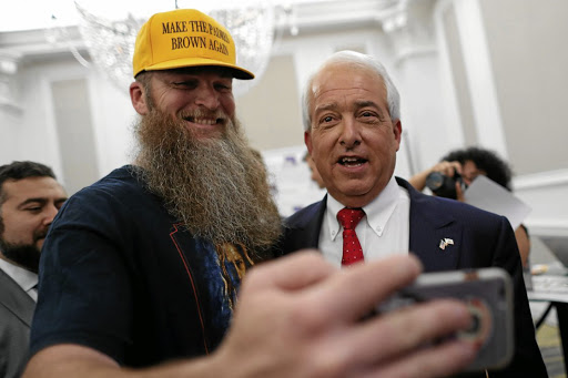 Republican gubernatorial candidate John Cox, right, stops to pose for a picture at his election night headquarters in San Diego on June 5 2018. Picture: REUTERS