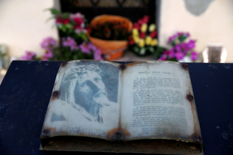 A prayer book is seen at the chapel beside 'L'arbre à loques', a 'healing' tree to which people attach cloths as a ritual for good health according to Celtic tradition, amid the Covid-19 pandemic in Hasnon, France. Picture: REUTERS/Pascal Rossignol