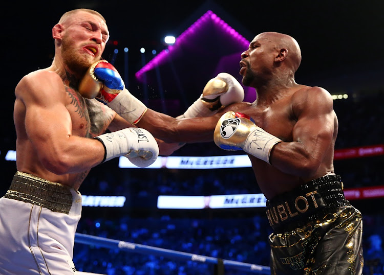 Floyd Mayweather Jr. lands a hit against Conor McGregor during a boxing match at T-Mobile Arena.