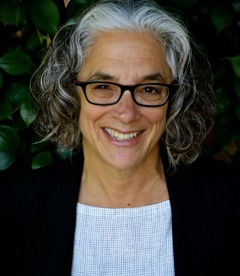 Lainey Feingold in front of green backdrop, wearing black glasses, and a balck and white shirt, smiling.