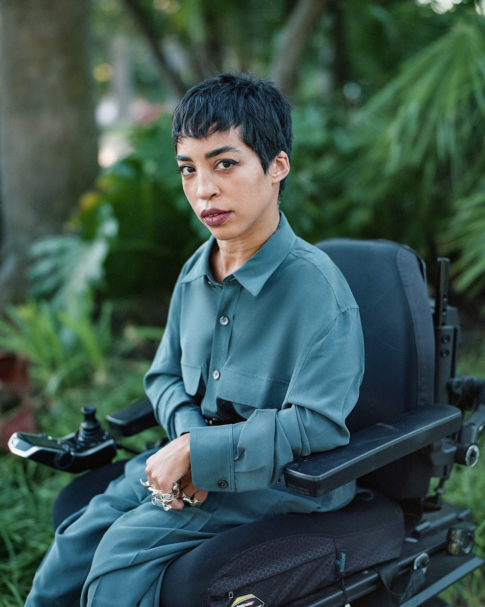 Jillian Mercado, founder of Black Disabled Creatives, seated in wheelchair with foliage in background.
