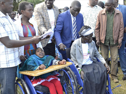 Nandi governor Stephen Sang (in blue suit) distributes wheelchairs in Kapsabet on Monday /BARRY SALIL