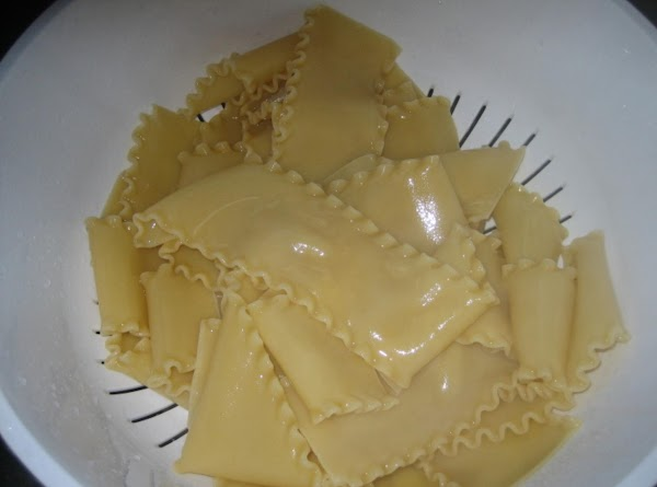 Boil lasagna noodles until they're about 1/2 way done.  Drain, rinse, and set...