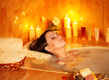 A woman smiling as she relaxes in a bath surrounded with lit candles
