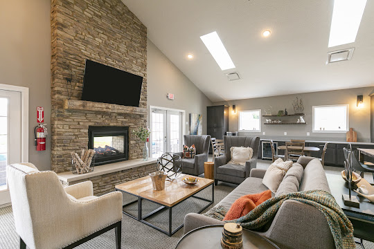 Interior clubhouse lounge with grey couch, grey chairs, white chair, fireplace, and tv