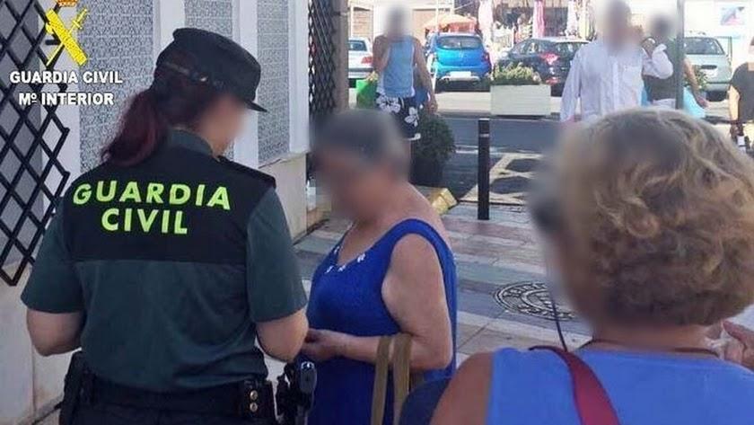 Una agente atiende a una mujer de avanzada edad.