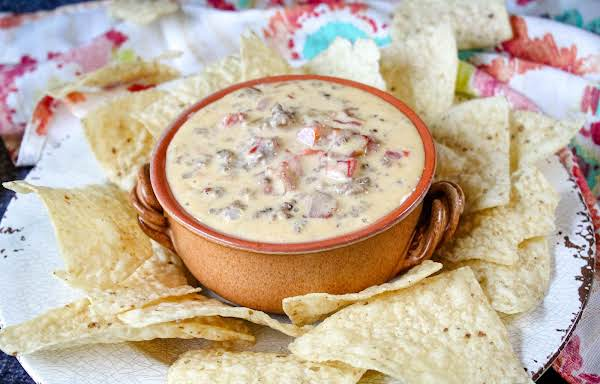 Bacon Cheeseburger Queso In A Bowl With Tortilla Chips.