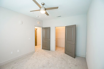 C1 bedroom with neutral carpet and ceiling fan