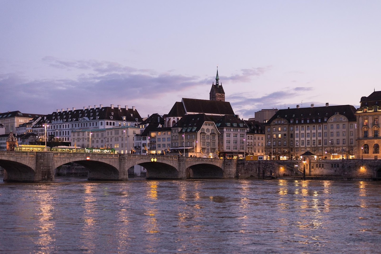 basel's old town medieval traditional architecture buildings seen from across bridge on the other side of river during sunset in switzerland