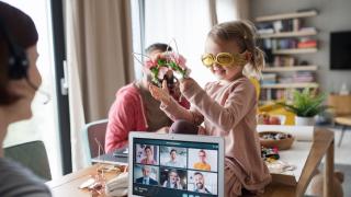 imagen de una niña de frente sentada en la mesa mientras una mujer hace una videollamada